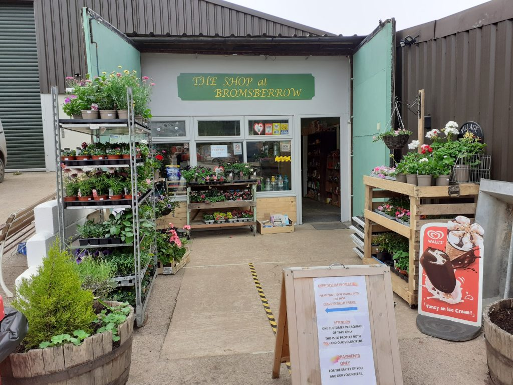 Photograph of the shop entrance. Yellow lettering on a green sign across the entrance says 'The Shop at Bromsberrow'. There are plants for sale on shelves to the left and right of the entrance.