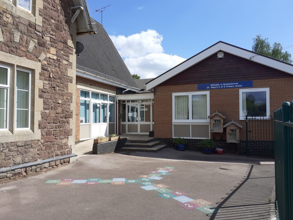 Entrance to school buildings made from natural stone and facebrick. White writing on a blue sign across the top of the building says 'Welcome to Bromsberrow St Mary's C of E Primary School'
