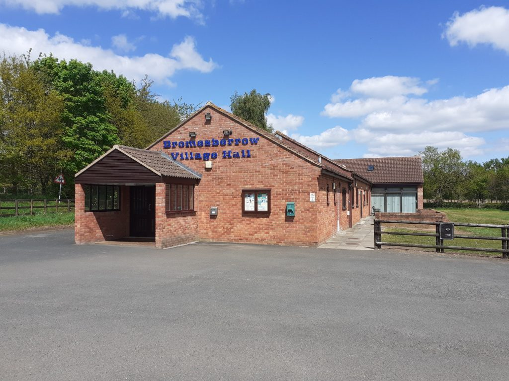 Photograph of front of facebrick building. Blue lettering across the front of the building says Bromsberrow Village Hall.