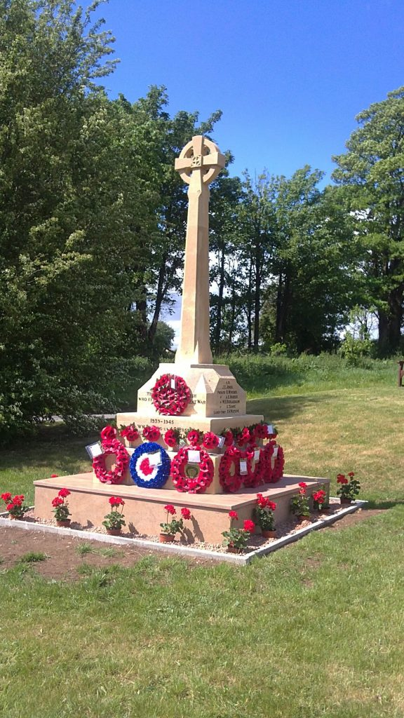 A Picture of the war memorial in Bromsberrow with rememberance day poppy wreaths around the base